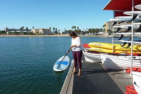 Getting on paddle board from pier